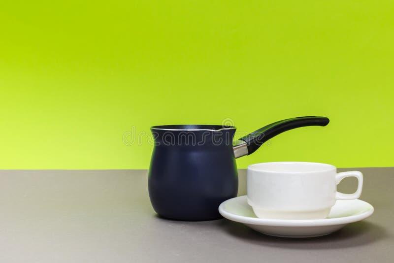 Nuevo pote del caf? del metal y taza blanca de la porcelana en una tabla gris y un fondo verde imágenes de archivo libres de regalías