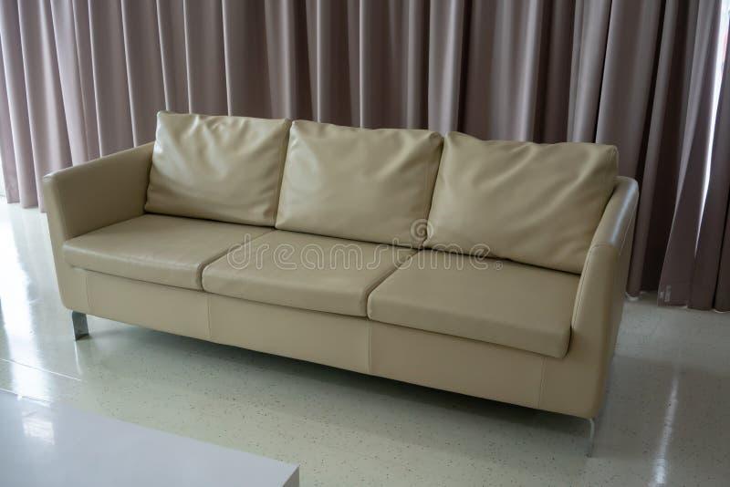 Nuevo sofá del cuero blanco en el piso blanco contra curta marrón claro fotografía de archivo libre de regalías