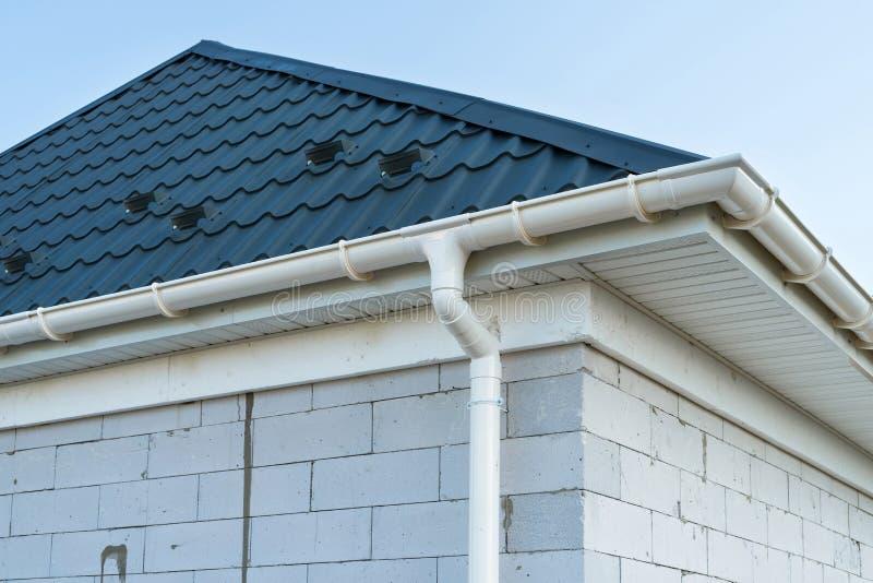 Nuevo tejado de teja del metal con el canal blanco de la lluvia Construcci?n de la casa del panel del SORBO Edificio inacabado foto de archivo