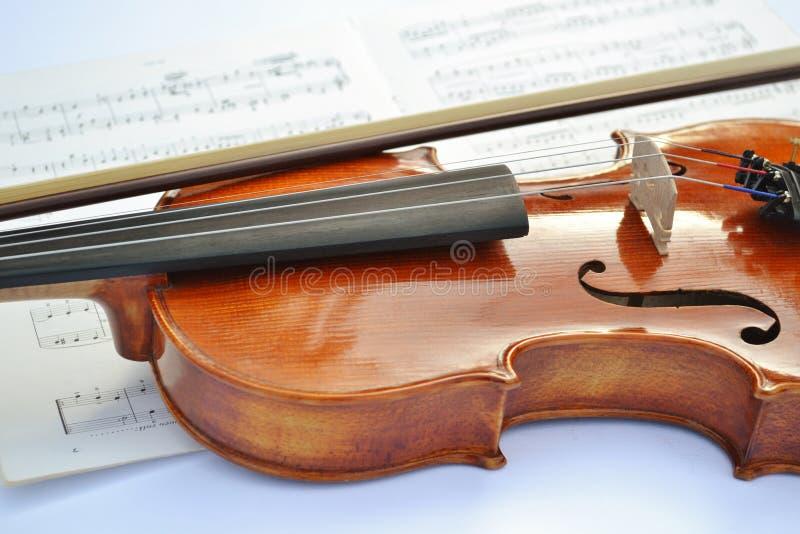 Nuevo violín de madera marrón con un arco puesto a lo largo del instrumento de música y de una partitura bajo ella imágenes de archivo libres de regalías