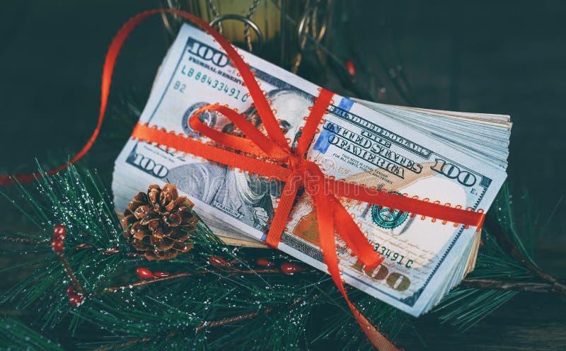 Nuevo Year& x27; dolllars de los E.E.U.U. del regalo 100 de s contra la perspectiva de la moneda americana fotos de archivo libres de regalías