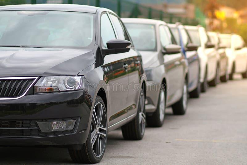 Nuevos coches parqueados delante de un coche, tienda del distribuidor autorizado del motor, tienda en cola fotos de archivo