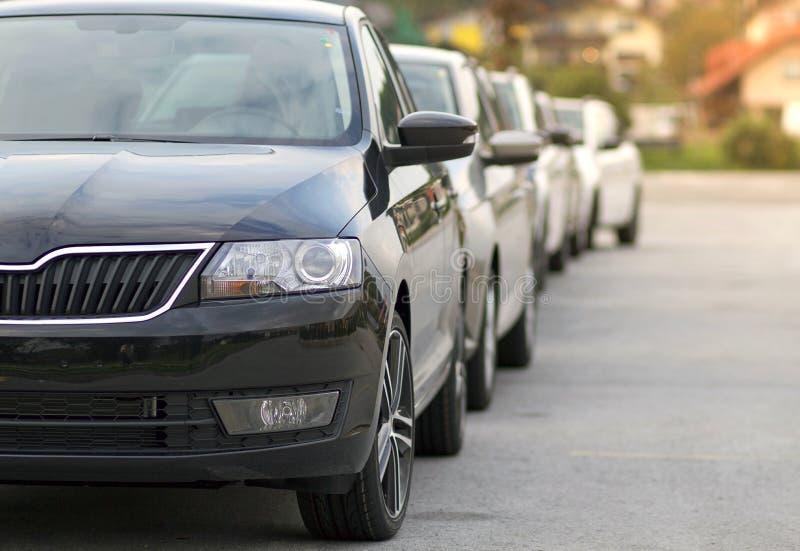 Nuevos coches parqueados delante de un coche, tienda del distribuidor autorizado del motor, tienda en cola imagenes de archivo