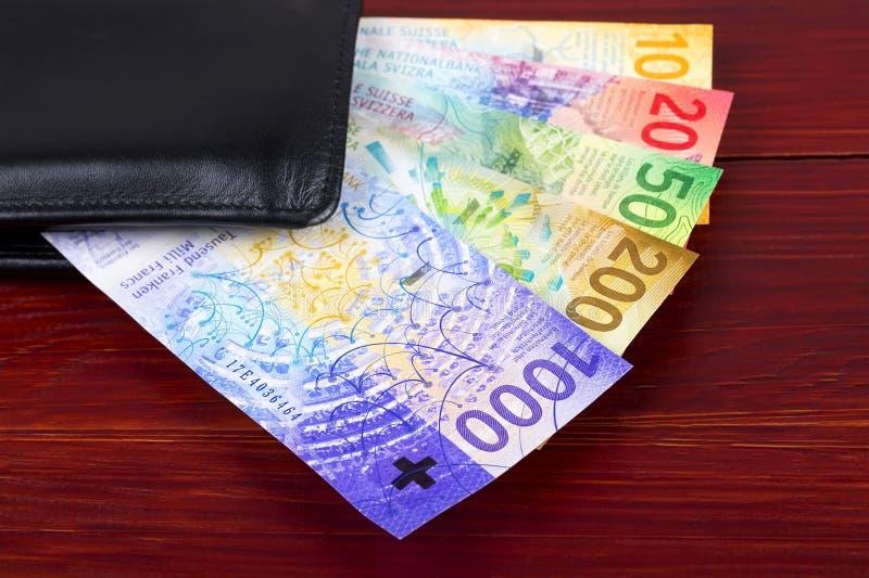 Nuevos francos suizos en la cartera negra fotos de archivo