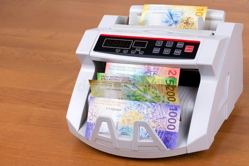 Nuevos francos suizos en una máquina de cuenta foto de archivo