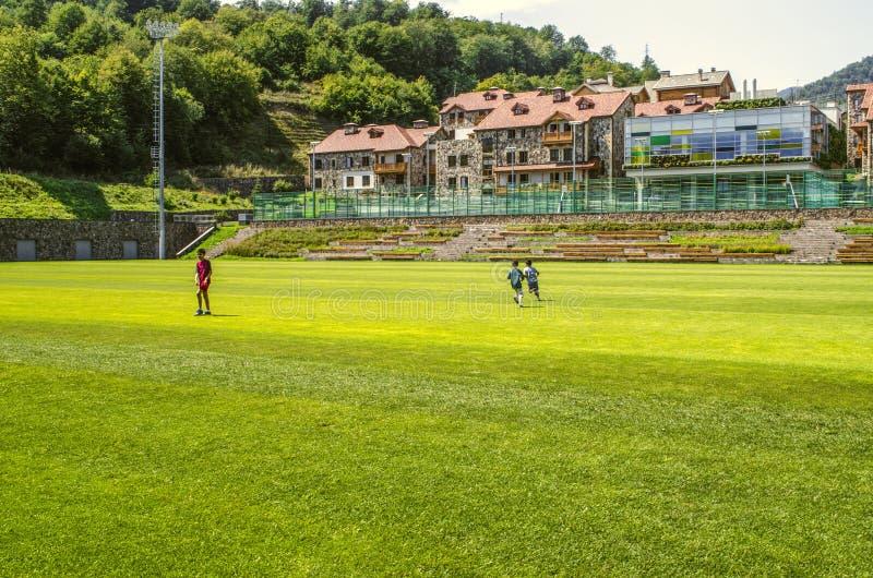 Nuevos paradores y un comedor para los estudiantes enfrente del campo de fútbol con los campos de tenis en la universidad interna fotografía de archivo libre de regalías