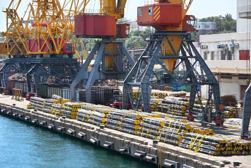 Nuevos tubos en el puerto, las grúas del cargo y la infraestructura industriales foto de archivo libre de regalías