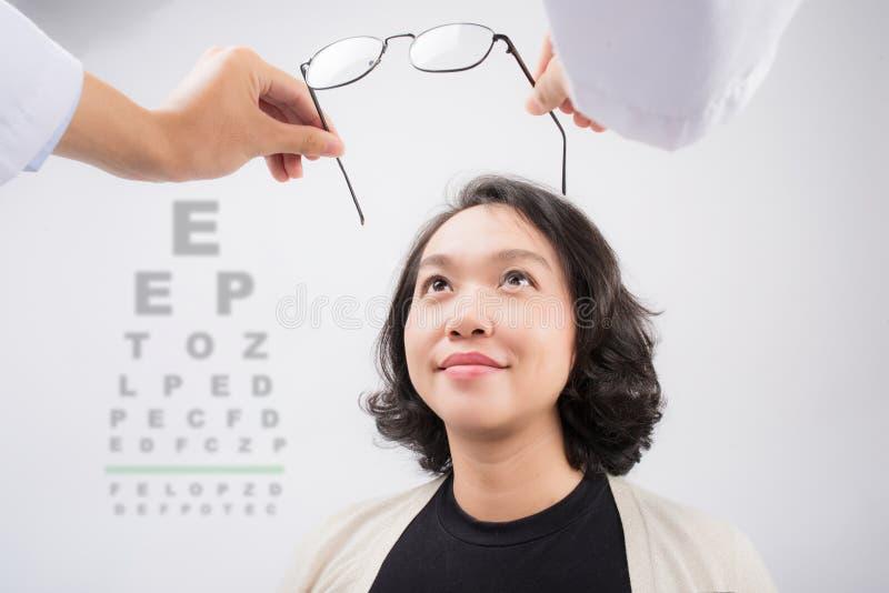 Nuevos vidrios Optometrista que da las lentes asiáticas de la mujer para intentar imagen de archivo