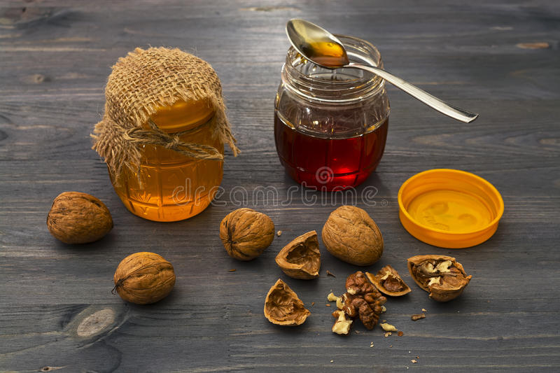 Nuez y miel Un pote de miel en la tabla fotos de archivo libres de regalías