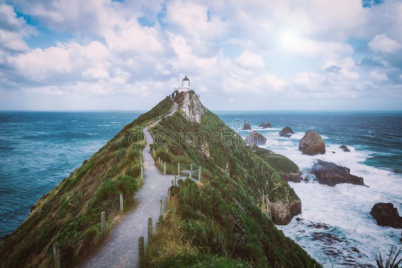 Nugget Point lighthouse trail and rocks in the ocean in Otago stock image