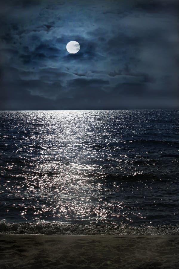 Nuit éclairée par la lune par la mer images stock