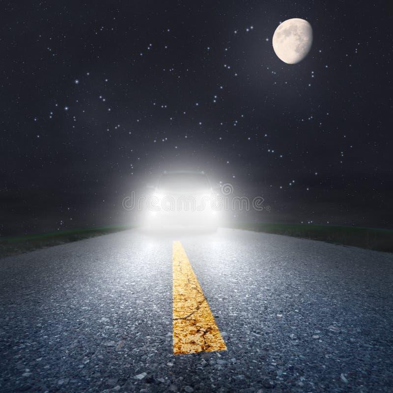 Nuit conduisant sur une route goudronnée vers les phares photographie stock