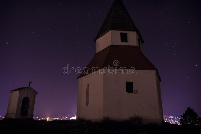Nuit de ville du point de vue sur la colline avec la chapelle Ville slovaque Nitra avec le ciel nocturne pourpre avec des étoiles image stock