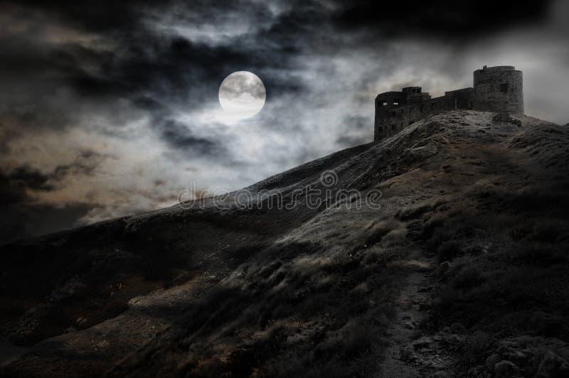 Nuit, lune et forteresse foncée photographie stock
