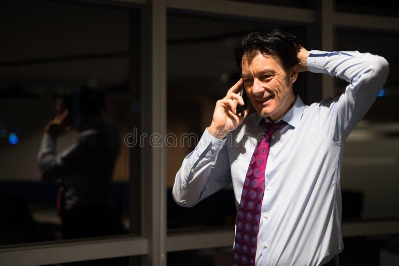 Nuit mûre d'In Office At d'homme d'affaires parlant au téléphone portable photographie stock