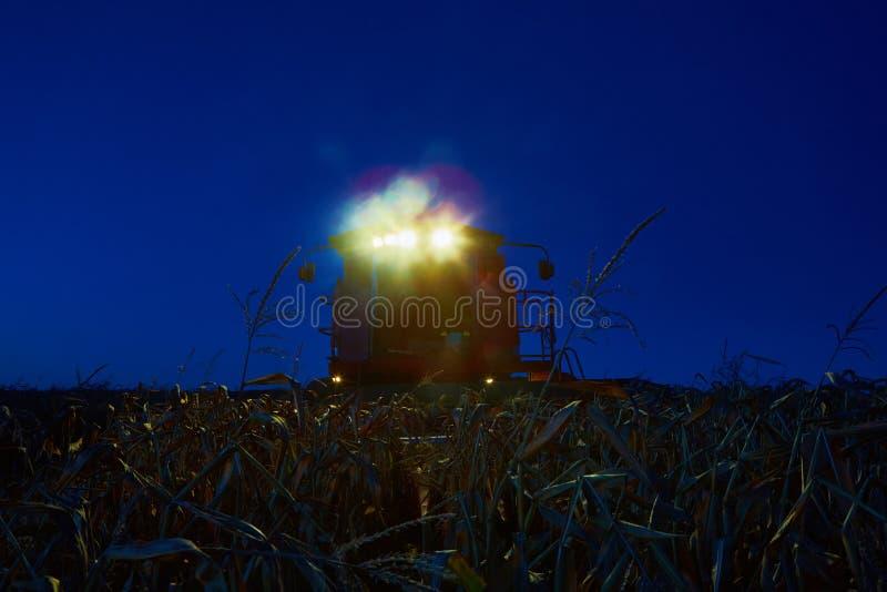 Nuit moissonnant dans les domaines Cartels avec des lumières dans le mouvement vers la fin de la soirée photographie stock