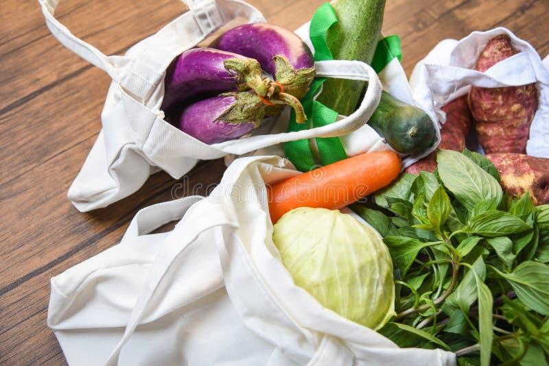 Nul plastic concept van het afvalgebruik minder/Verse groenten organisch in eco katoenen stoffenzakken op houten lijst stock foto's