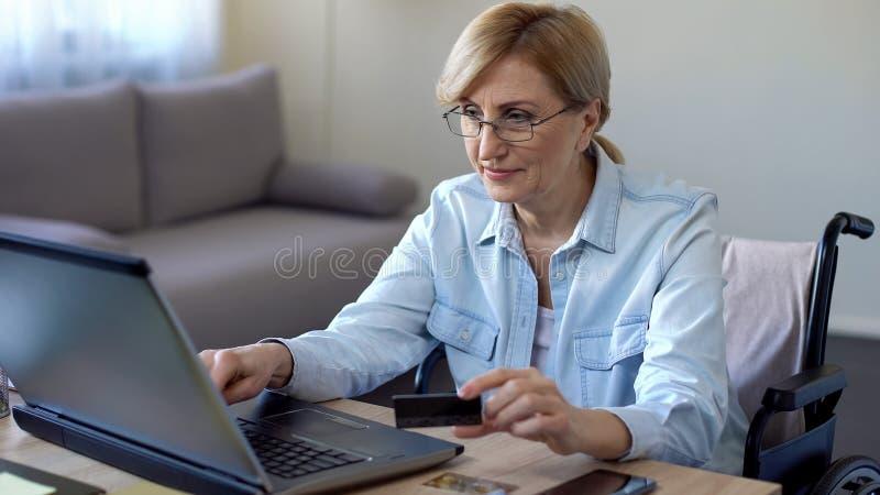 Numéro de carte entrant de crédit de femme supérieure sur l'ordinateur portable, service pour des handicapés photos stock