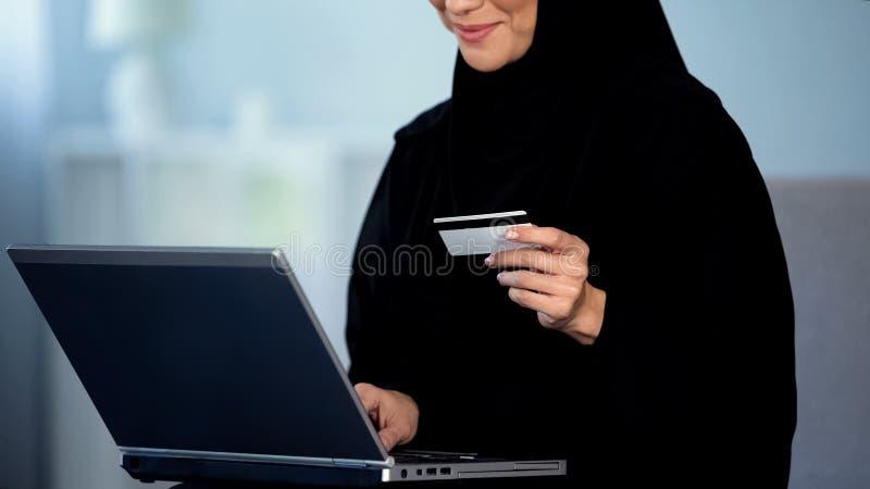 Numéro de carte entrant de jeune dame arabe sur l'ordinateur portable, hôtel de réservation en ligne, paiement photo stock