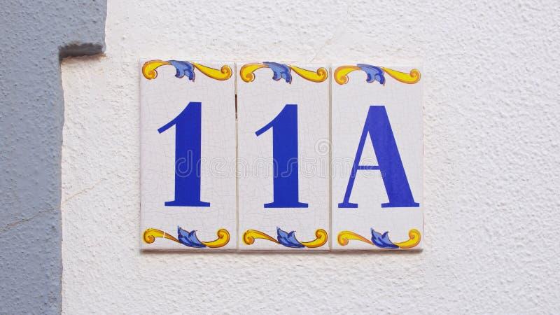 Numéro de maison de céramique sur le mur onze photos libres de droits