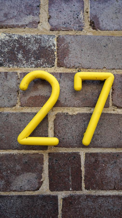 Numéro de maison sur le mur de briques - vingt-sept dans des chiffres jaunes images stock