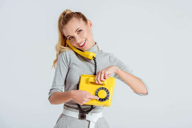 numéro de téléphone de composition de femme au téléphone jaune de cru d'isolement photographie stock libre de droits