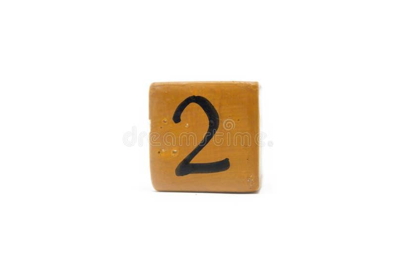 Numéro deux sur le cube de matériel en bois d'isolement sur le fond blanc image libre de droits