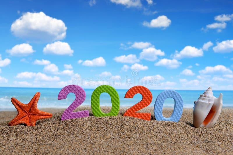 Numéro 2020 et coquille de mer avec des étoiles de mer sur la plage de sable photographie stock