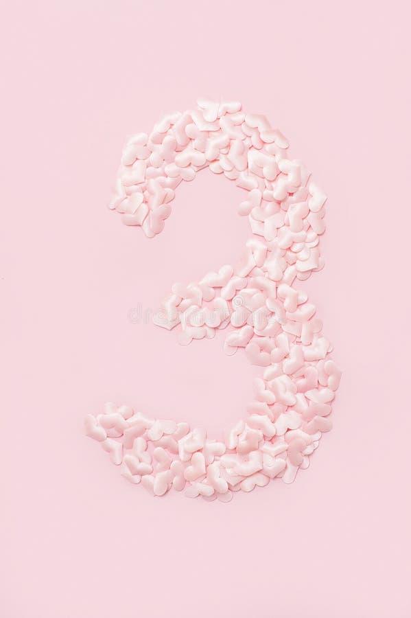 Num?ro trois rassembl? des coeurs roses d?coratifs D'isolement sur le fond rose photographie stock