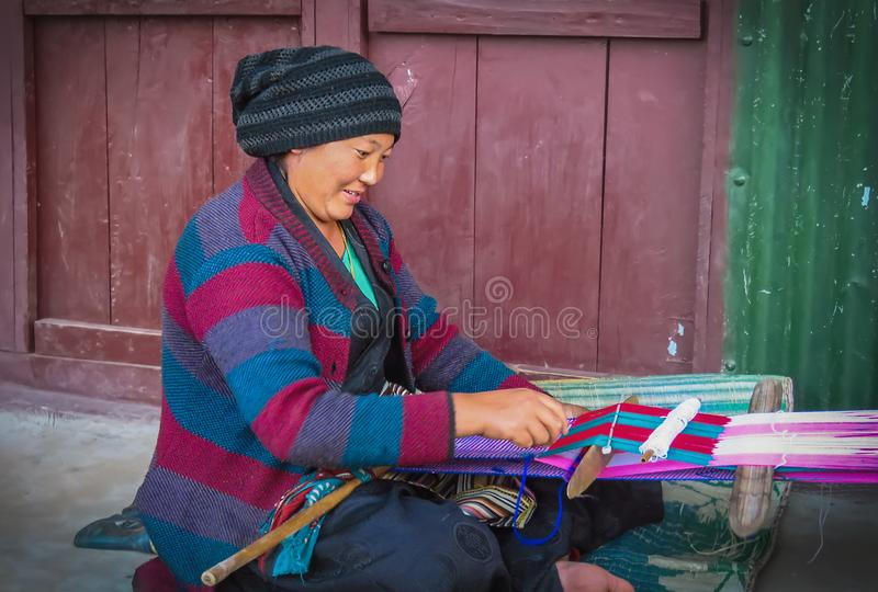 Woman manually weaving a piece of cloth sitting outside on the ground in a small mountain village in East-Nepal. Num, Nepal - 11/17/2017: woman manually weaving royalty free stock photo
