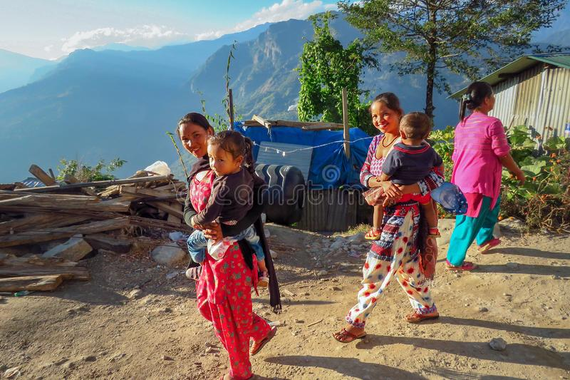 Nepalese women in colorful clothes carrying child while walking outside i. Num, Sankhuwasabha District, Nepal - 11/17/2017: Two Nepalese women in colorful royalty free stock photography