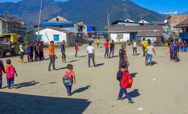 Teenagers playing at the town square of a remote mountain village, Num, Nepal. Num, Sankhuwasabha District, Nepal - Young men playing a ballgame while children stock photo
