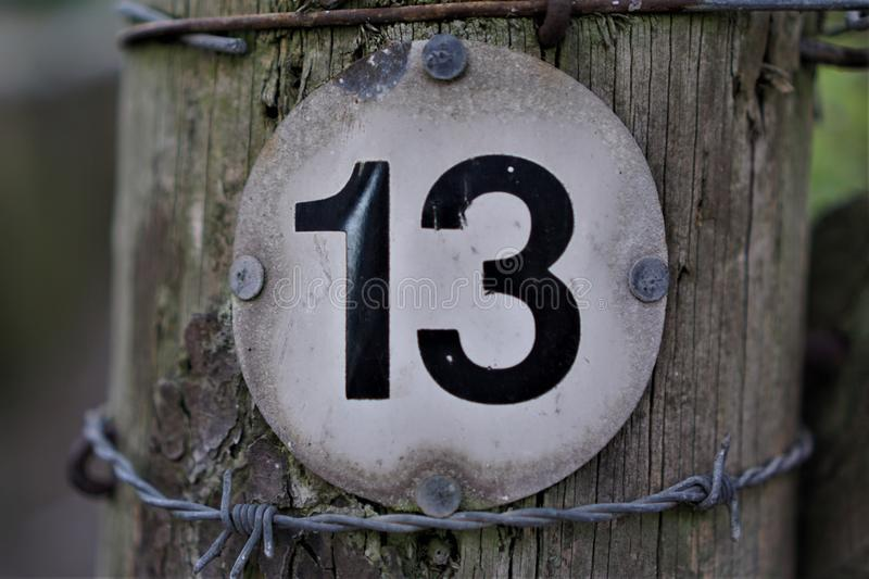 Number 13 in circle shaped board. On wooden bollard stock photos