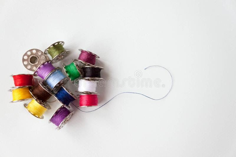 Number of different colors colorful multicolored sewing thread on metal spools on light blue background. Selective soft focus,. Row of number of different colors royalty free stock photo