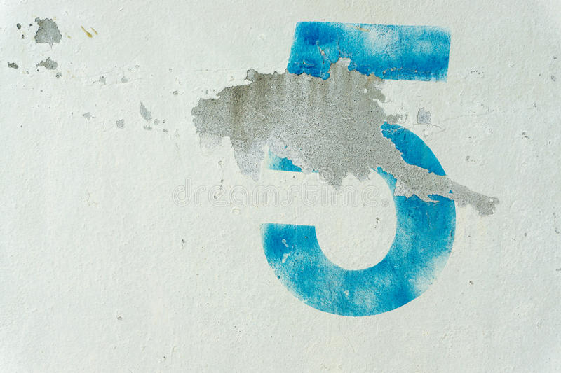The number 5 on the dirty white wall royalty free stock photography