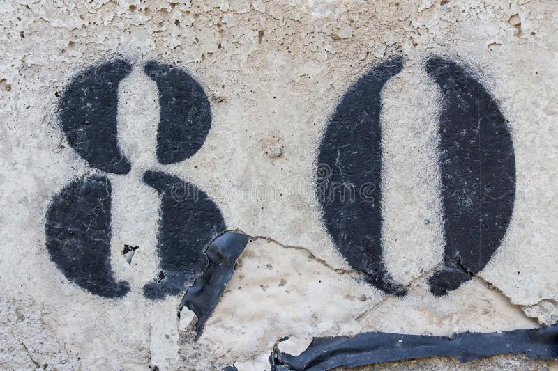 Number eighty painted stencil on concrete wall. Number 80 royalty free stock photo