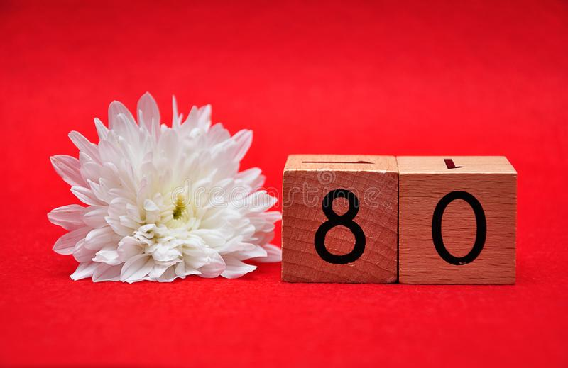 Number eighty with a white daisy. On a red background stock photos