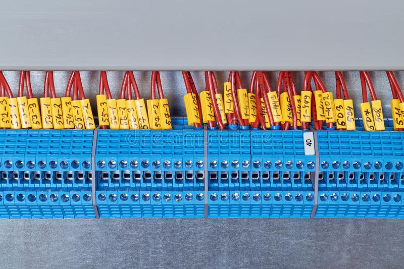 A number of electrical transmission terminals with electrical wires attached to them. Lot electrical feed-through terminals, arranged in a row. To them are stock photo