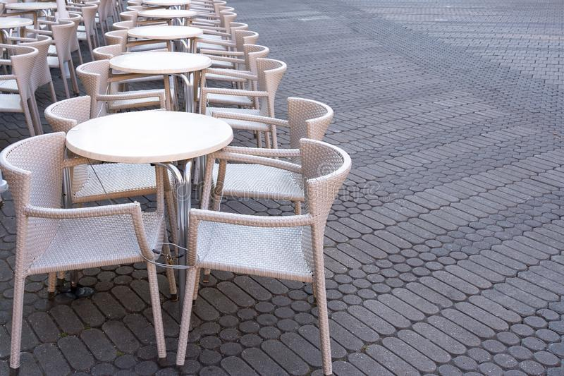 A number of empty tables with chairs are connected by a cable from theft in a cafe on the street stock images