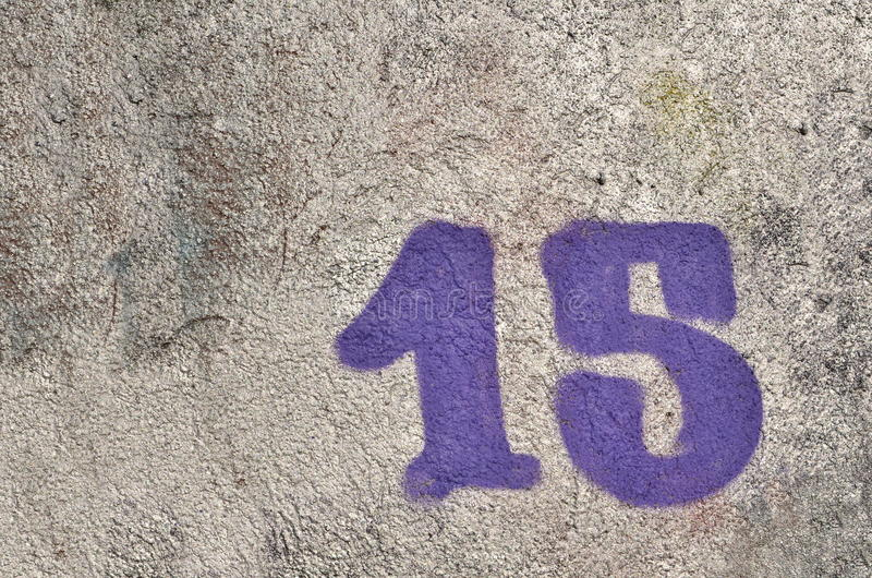 Number 15. Fifteen of purple color airbrushed with graffiti paint over silver background on textured wall royalty free stock photo