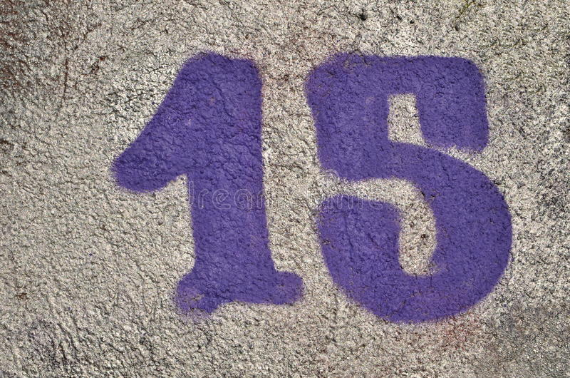 Number fifteen. Number 15 fifteen of purple color airbrushed with graffiti paint over silver background on textured wall stock photography