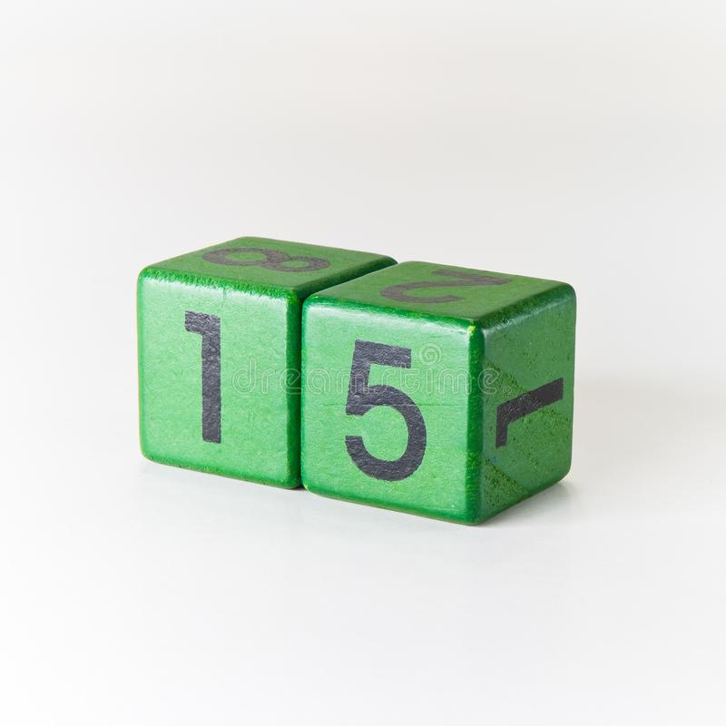 Number fifteen written on a wooden green cube on white background stock photography