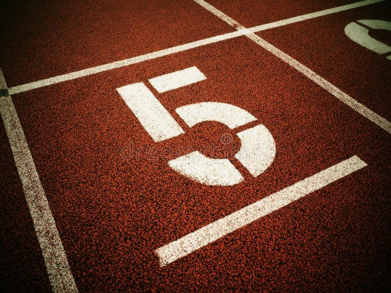 Number five. Big white track number on red rubber racetrack. Gentle textured running racetracks in small athletic stadium royalty free stock image