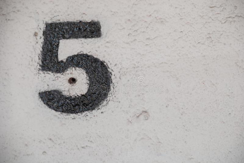 Number five painted in black on a white wall royalty free stock photo