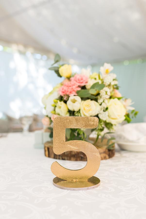 Number five at table for guests on wedding hall. Gold wedding table number. stock image