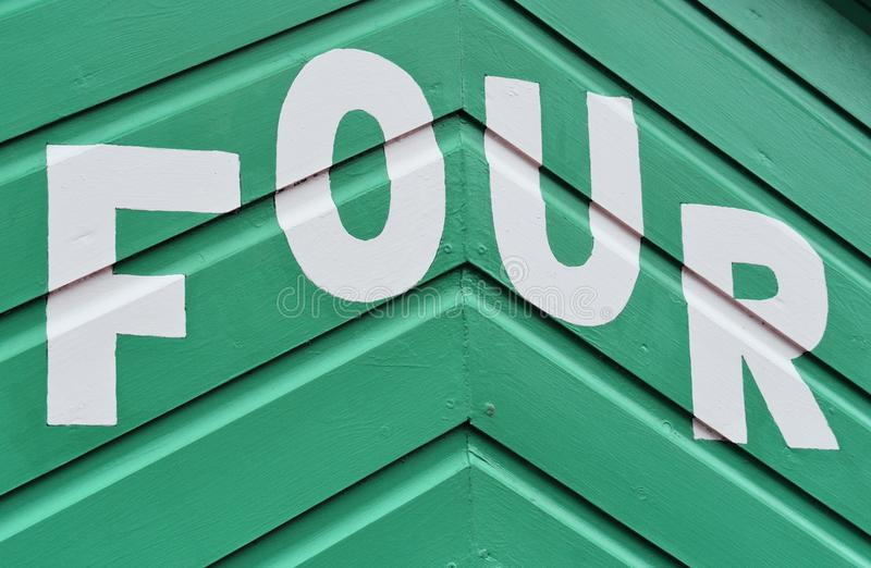 Number FOUR in letters written on the side of a wooden beach hut. The number FOUR in white capital lettering written on the side of a green wooden beach hut stock photos