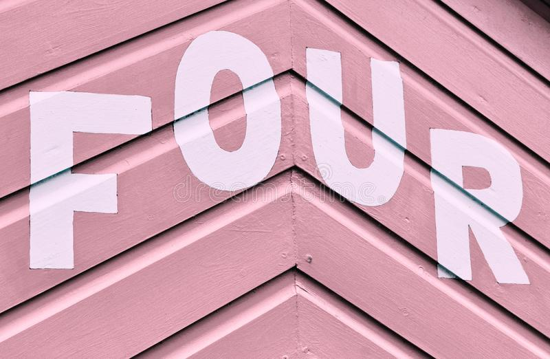 Number FOUR in letters written on the side of a wooden beach hut. The number FOUR in white capital lettering written on the side of a pink wooden beach hut royalty free stock image