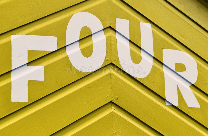 Number FOUR in letters written on the side of a wooden beach hut. The number FOUR in white capital lettering written on the side of a yellow wooden beach hut royalty free stock photo