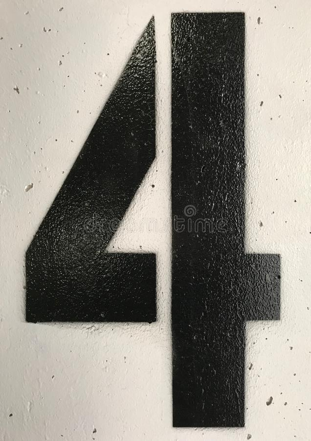 The Number Four in Spraypaint. Spraypaint number four in a parking garage in black with white background stock images