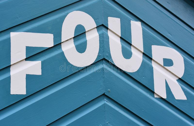 Number FOUR in letters written on the side of a wooden beach hut. The number FOUR in white capital lettering written on the side of a blue wooden beach hut royalty free stock photos